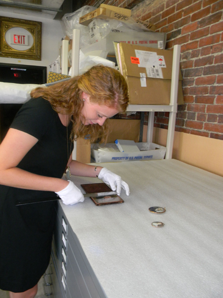 Intern Allison Murphy examines miniatures from the Gibbes collection.