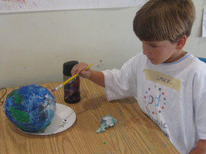 Shep paints a papier-mache globe during Go Green week.