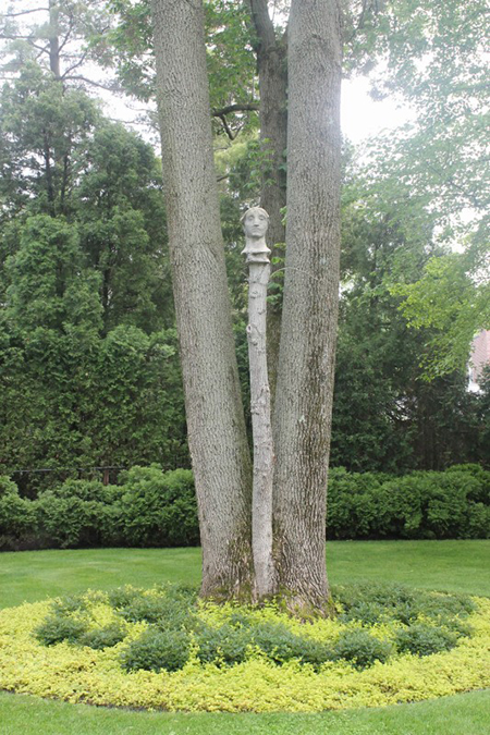 whimsical sculpture towers among the tree trunks