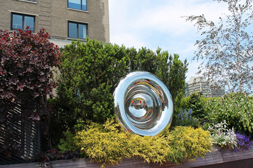 A mirrored sculpture installed on a private rooftop garden in downtown Chicago.