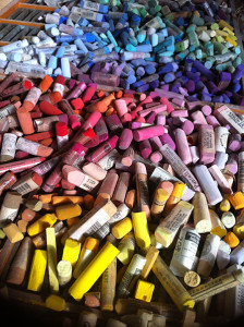 A colorful array of soft pastel (not chalk) in an artist's tool box