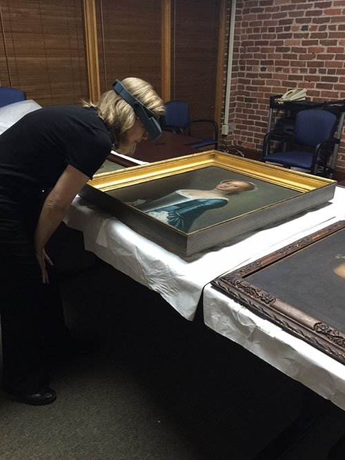 Shelley reviewing Jeremiah Theus paintings from the Gibbes permanent collection