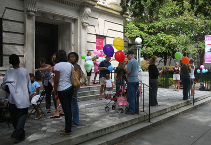 Visitors gather on the front steps to listen to banjo and guitar performers Lowcountry Bluegrass, to grab a balloon, and to get their face painted before moving inside