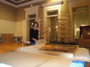 Collections Manager Zinnia Willits unwrapping a slip-cased painting