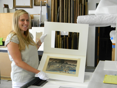 Sarah West, a summer intern in the Curatorial and Collections Departments, handles a woodblock print by Hokusai in the Gibbes collection.