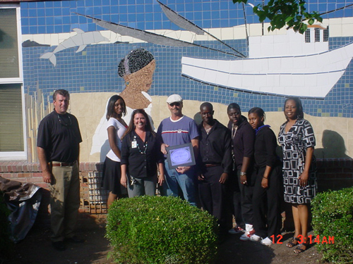 Artists in front of a mosaic mural at the Lincoln Middle-High School.