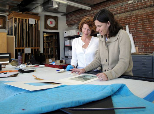 Zinnia Willits and Sara Arnold assess the condition of an outgoing loan object.