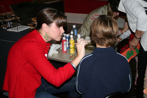A volunteer helps with face painting activities.