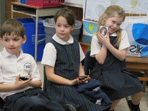 BSS second graders Leo Sparacino, Lauren Nadeau and Maria Alexander consider their miniature portraits.