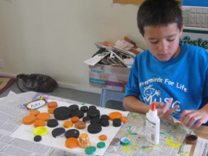Alex creates a collage with recycled screw-caps during Go Green week.