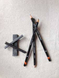 Drawing implements: graphite sticks, charcoal, and pencils.