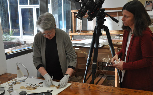 Conservator and curator examine miniature portraits