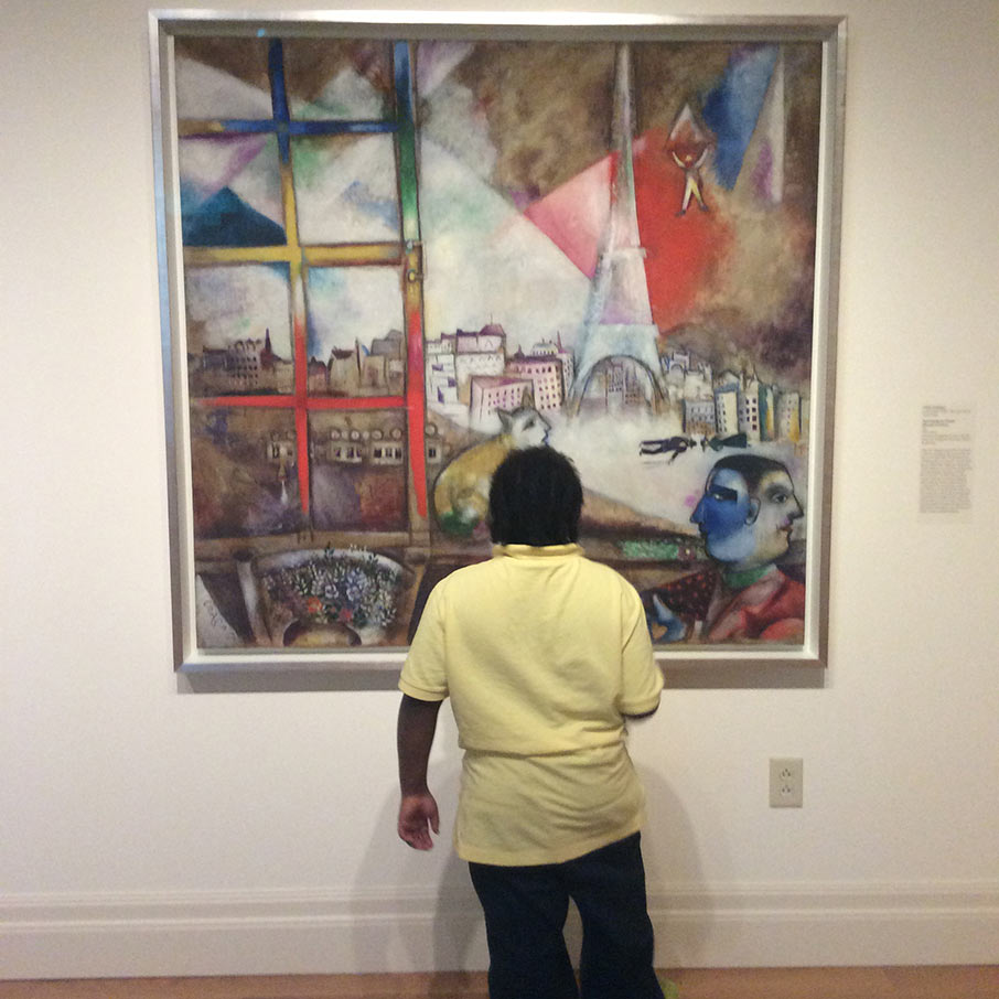 A student from Murray-LaSaine Elementary School captivated by Chagall's painting, Paris through the Window.