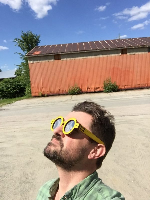 "Artist Michael Zebrowski models the ""Hockney"" style of Surveyor eclipse viewing glasses."
