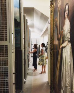 Zinnia Willits showing visitor the painting storage racks